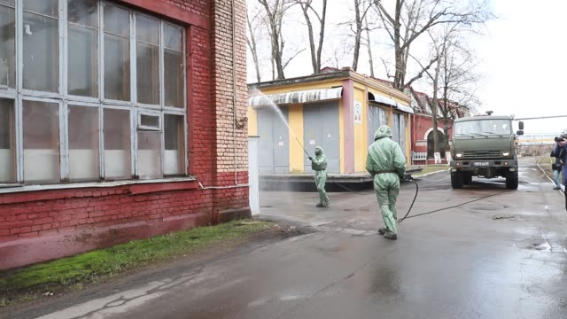 russian soldiers wearing protective suit disinfects a territory of a october train factory on april 15, 2020 in saint petersburg, russia - russia点の映像素材/bロール