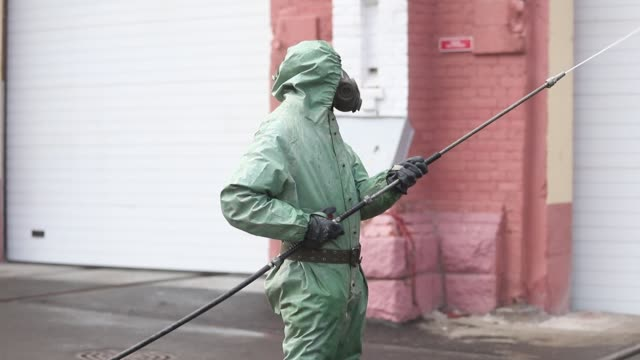 russian soldiers wearing protective suit disinfects a territory of the october train factory on april 15, 2020 in saint petersburg, russia - russia点の映像素材/bロール