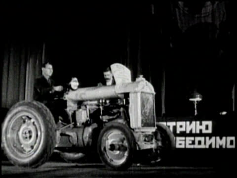 a russian tractor drives onto a stage / russian audience cheers / a crane lifts a large crate / workers guide the crate down / crates from chevrolet... - chevrolet stock videos & royalty-free footage