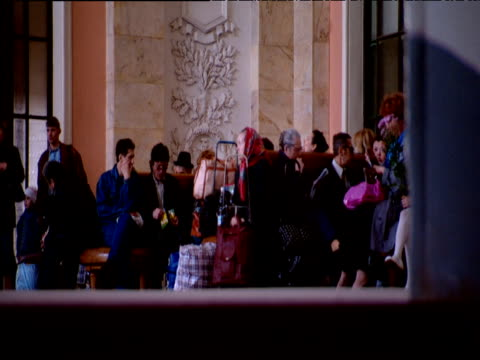 Russian train passengers sit in waiting area in train station as feet walk past camera in foreground St Petersburg