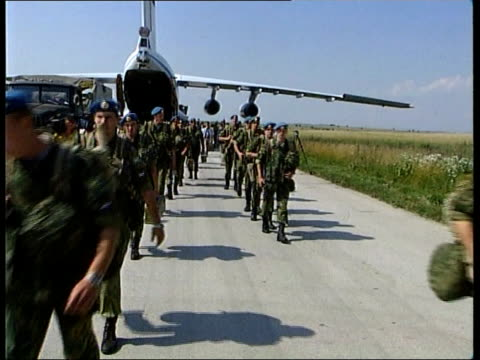 russian troops arrive russian troops arrive yugoslavia kosovo pristina gvs russian troops along from plane with equipment soldiers picking up... - geschlechtskrankheit stock-videos und b-roll-filmmaterial