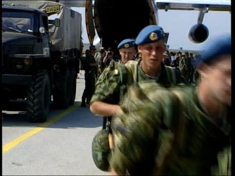 russian troops arrive russian troops arrive yugoslavia kosovo pristina gvs russian troops along from plane with equipment soldiers picking up... - pristina stock videos and b-roll footage