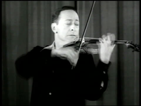 vídeos de stock e filmes b-roll de russian violinist jascha heifetz playing the violin w/ man on piano ms heifetz playing cu hands on strings vs heifetz playing usa - 1947