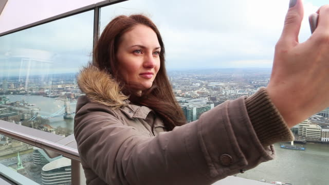 Russian woman taking selfie from London skyscraper with the city view during travel vacations.