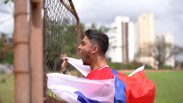 giovane russo che festeggia mentre tiene in mano la bandiera nazionale - eastern european culture video stock e b–roll