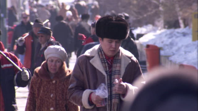 russians wear heavy winter coats and hats while walking downtown in astana kazakhstan russia available in hd. - kazakhstan stock videos and b-roll footage