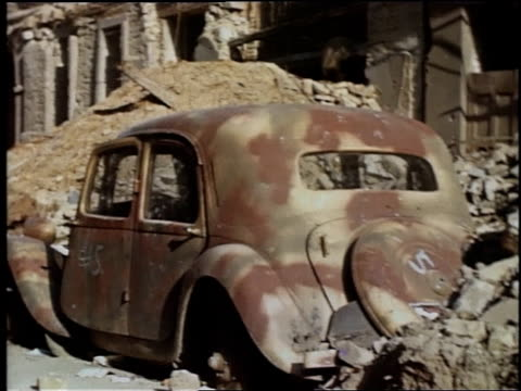 ws rusted and destroyed car buried under rubble / wiesbaden germany - wiesbaden stock-videos und b-roll-filmmaterial