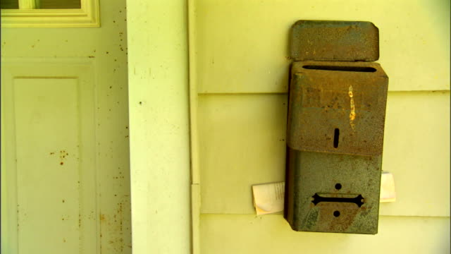 MS Rusted looking mail letterbox hanging frame next to door of unidentifiable yellow house Mailbox