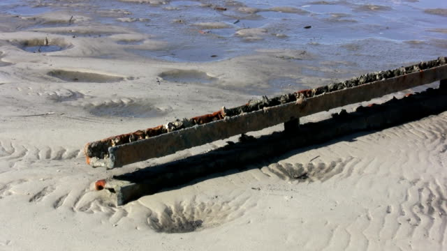Rusted Metal Railway Track Lying on a Deserted Beach