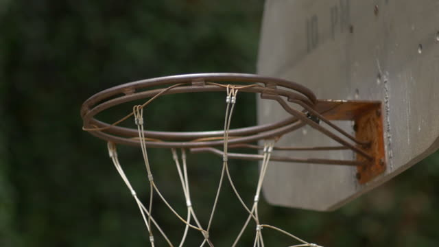 A rusted rim on an urban outdoor basketball hoop. - Slow Motion