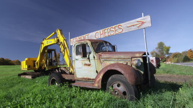 Rusted truck in field with sign about Vermont Cheese on a sunny day