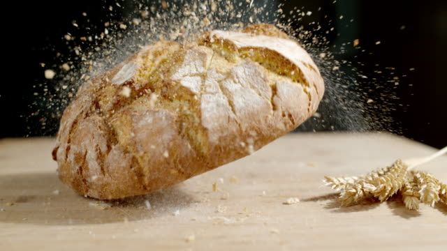 slo mo rustic crusty round bread falling on a table - bread stock videos & royalty-free footage