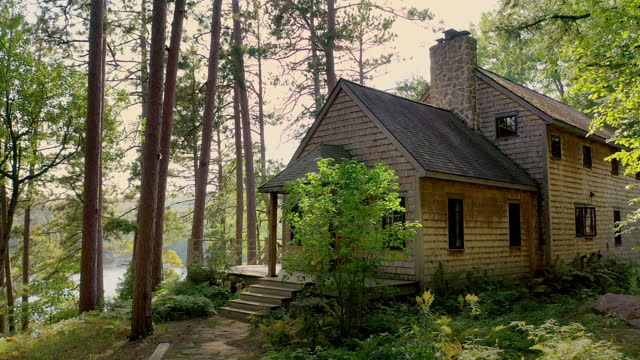 rustic house in the woods above a lake - stone house stock videos & royalty-free footage