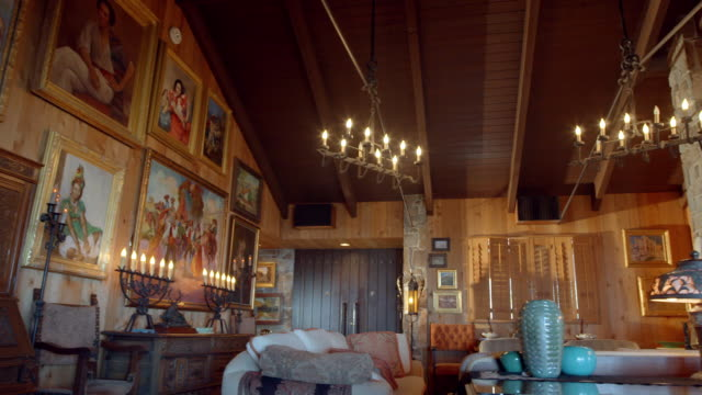ws ds  rustic, mid-century lodge with collection of california themed paintings on all walls, natural stone fireplace, cathedral ceiling and antique furnishings - chalet video stock e b–roll