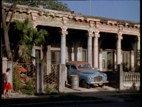 vidéos et rushes de rusting car parked in front of ornately decorated but dilapidated buildings havana; 1970's - cuba