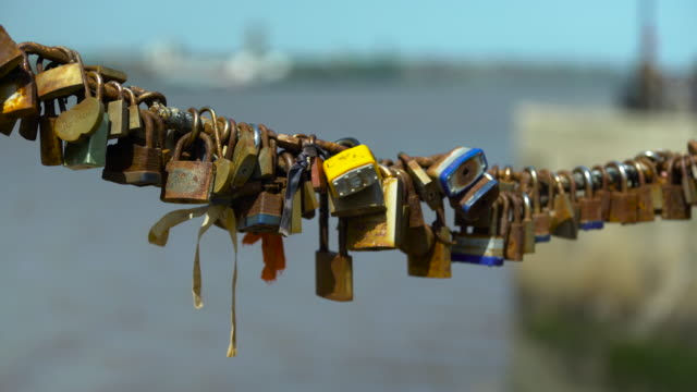 rusty love locks on chain fence by river - 幸運点の映像素材/bロール