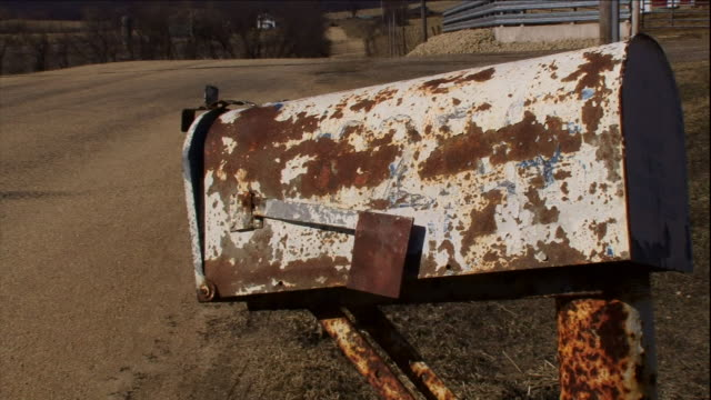 a rusty mailbox leans at the side of a dirt road. - imperfection stock videos & royalty-free footage