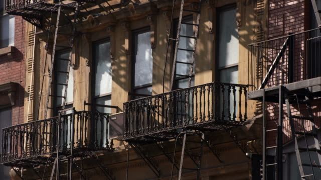 a rusty old fire escape on the side of an apartment building - fire escape stock videos & royalty-free footage