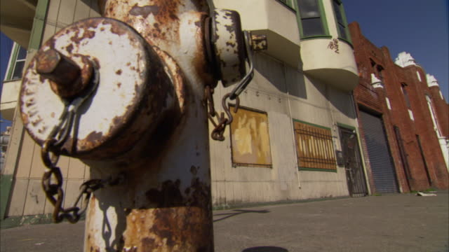 rusty weathered fire hydrant in fg boarded building in bg on city street - oakland california stock videos & royalty-free footage