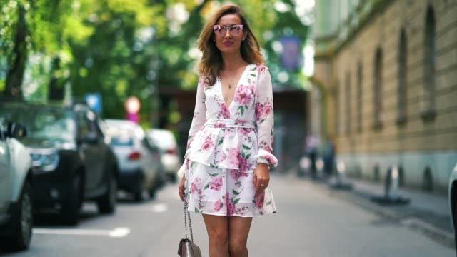 ruxandra chis wears a white dress with floral pink prints, a silver bag , during feeric fashion week 2018, on july 21, 2018 in sibiu, romania. - 白のドレス点の映像素材/bロール