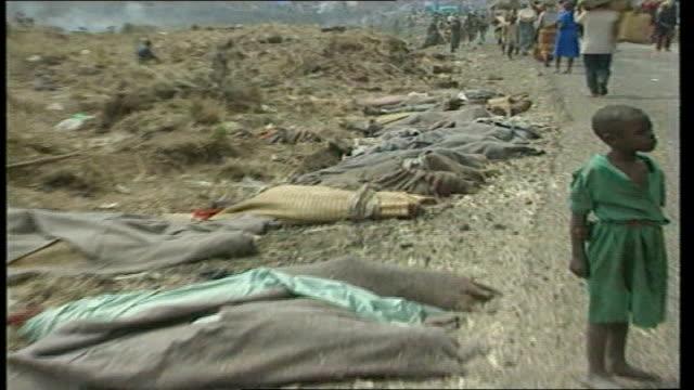 rwanda massacre suspects held in britain; tx 7.6.1994 rwanda: nyatama: trucks through tutsi refugee camp , bodies laid out at roadside in foreground... - 大量殺人点の映像素材/bロール