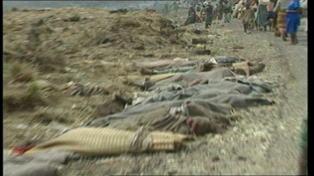 Rwanda massacre suspects held in Britain TX Nyatama Trucks through Tutsi refugee camp bodies laid out at roadside in foreground Skull amongst debris...