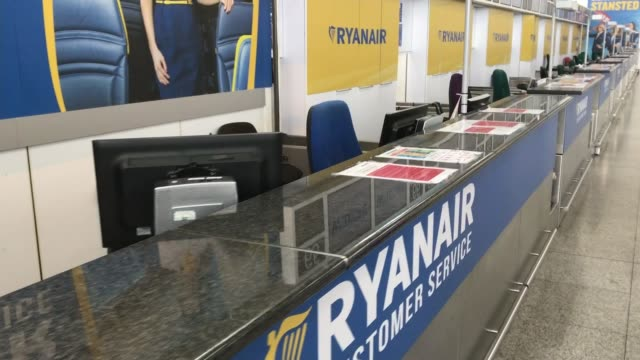 michael o'leary speaks at agm stansted airport ext airport vehicles on runway deserted ryanair customer service desk with 'here to help' sign ext... - jahreshauptversammlung stock-videos und b-roll-filmmaterial