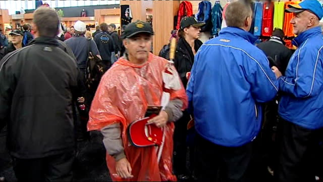 day one / play disrupted by rain INT American golf fans along in light rain macs and purchasing rainproof jackets in shop