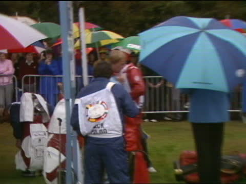 walton heath: ext / rain peter oosterhuis under umbrella nick faldo zoom-in under umbrella and pull-out jack nicklaus nicklaus at golf bag r-l crowd... - cheerful stock videos & royalty-free footage