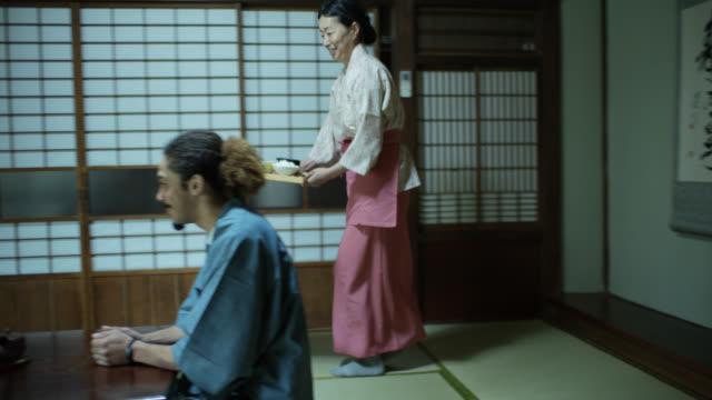 stockvideo's en b-roll-footage met ryokan gastvrouw serveert gasten - ryokan