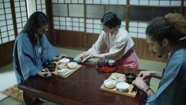 stockvideo's en b-roll-footage met ryokan gastvrouw serveert thee aan de gasten - ryokan