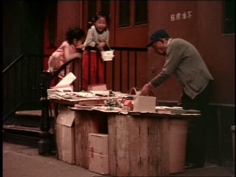 1950's 2 asian girls watching elderly street vendor / chinatown, san francisco - popolazione dell'asia orientale video stock e b–roll