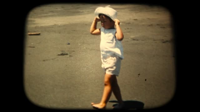 vídeos de stock e filmes b-roll de 60's 8mm footage - boy splashing in the sea - areia
