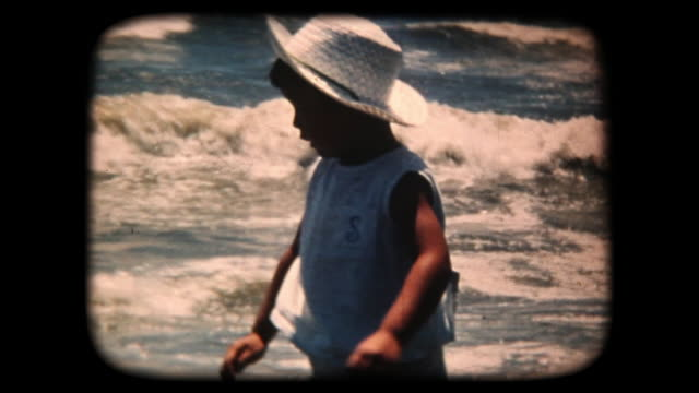 stockvideo's en b-roll-footage met 60 's 8 mm footage - boy spatten in the sea - retro style