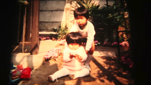 60's 8mm footage -helps baby sister walk - sibling stock videos and b-roll footage