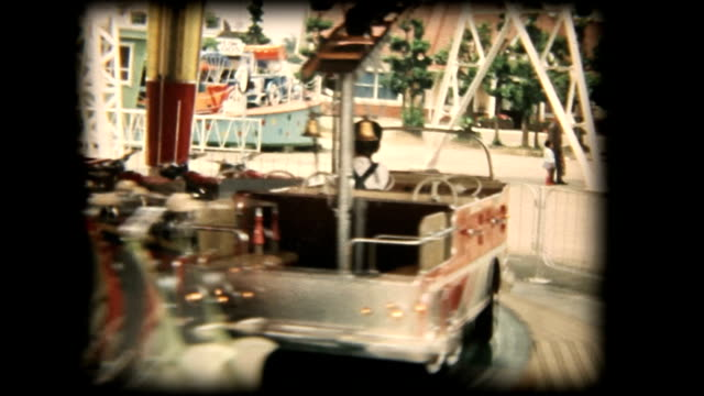 60's 8mm footage - young boy riding on a merry-go-round at amusement park.