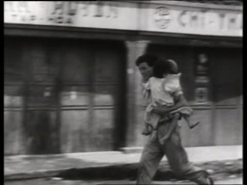 s asian man carrying 2 children running in street / saigon / no sound - guerra del vietnam video stock e b–roll