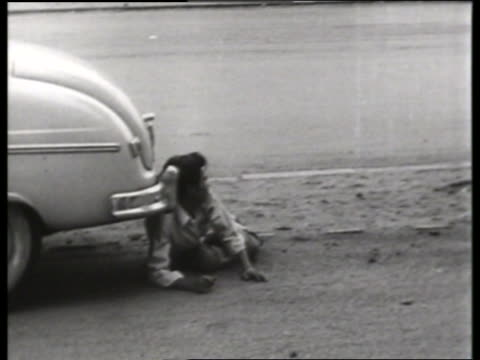 b/w 1960's asian man lying on ground near car / saigon / no - only mid adult men stock videos & royalty-free footage