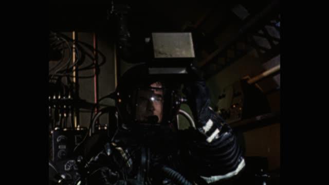 vidéos et rushes de 1950's astronaut talking on microphone while looking through an object in spaceship - décor de cinéma