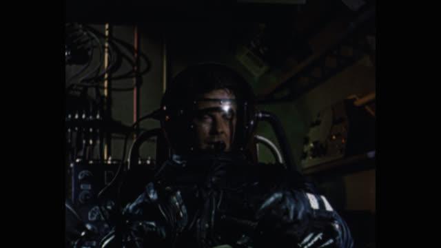 vidéos et rushes de 1950's astronaut talking on microphone while sitting in spaceship - décor de cinéma