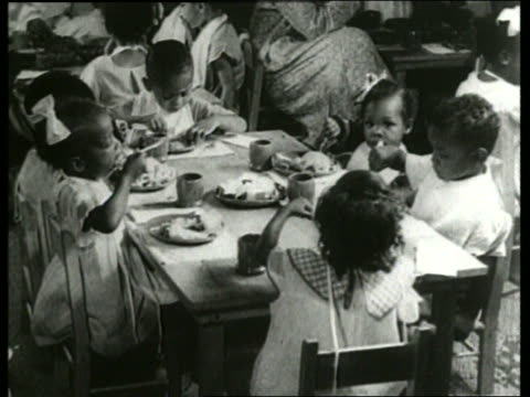 vídeos de stock e filmes b-roll de b/w 1930's black children eating at table / nursery school / sound - merenda escolar