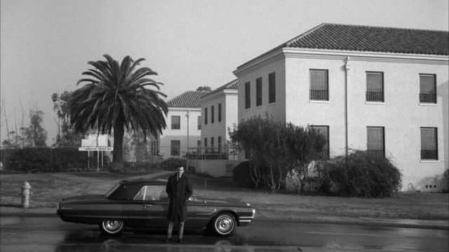 1960's B/W WS Man standing in front of car on street in residential district