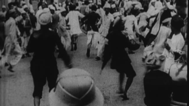 vídeos de stock e filmes b-roll de 1930's b/w montage british police beating people on streets of indian town / india - cultura britânica