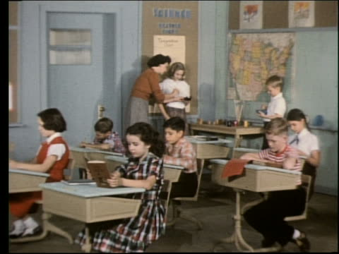 vídeos de stock e filmes b-roll de 1960's children reading books at desks in classroom / teacher background - professora