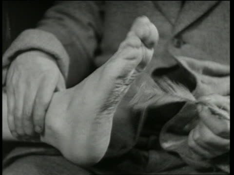 b/w 1930's close up man's hand tickling second man's foot with feather / corn on the cop - kitzeln stock-videos und b-roll-filmmaterial