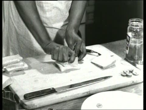 stockvideo's en b-roll-footage met b/w 1930's close up of black woman's hands making sandwiches / sound - huishuidkunde
