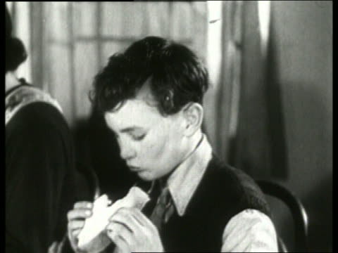 b/w 1930's close up of boy eating sandwich and turning head / no sound - sandwich stock videos & royalty-free footage