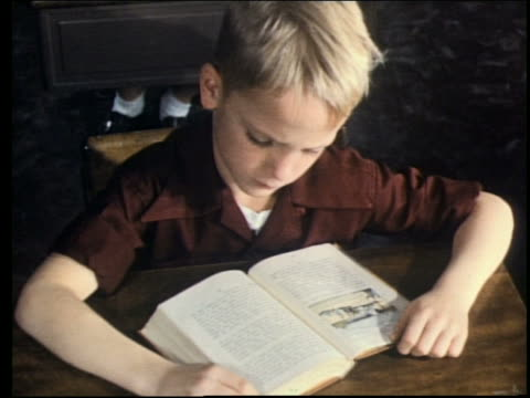 1960's close up of boy reading book at desk in classroom - elementary student stock videos & royalty-free footage