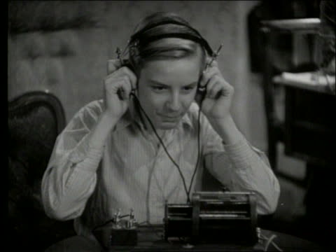 b/w 1950's close up of boy with headphones listening to crystal radio - モノクロ点の映像素材/bロール