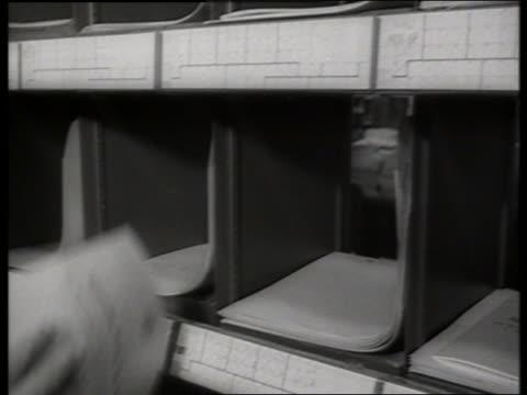 b/w 1960's close up of hands sorting booklets into slots / un / sound - einige gegenstände mittelgroße ansammlung stock-videos und b-roll-filmmaterial